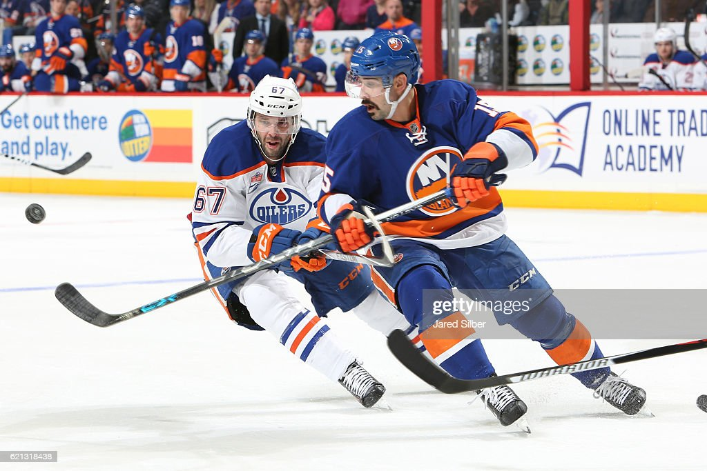 Cal Clutterbuck #15 of the New York Islanders battles for the puck against Benoit Pouliot #67 the Edmonton Oilers at the Barclays Center on November 5, 2016 in Brooklyn borough of New York City.