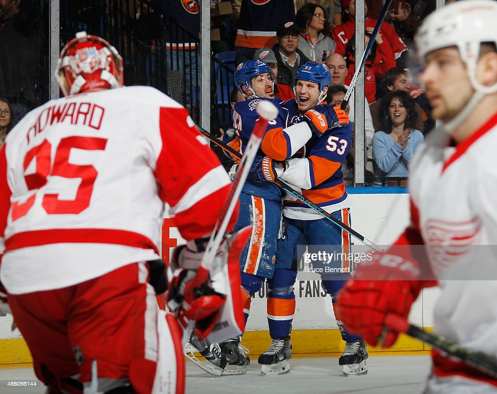 Cal Clutterbuck #15 of the New York Islanders (l) celebrates his shorthanded goal at 3:57 of the second period against Jimmy Howard #35 of the Detroit Red Wings as he is joined by Casey Cizikas #53 (r) at the Nassau Veterans Memorial Coliseum on March 29, 2015 in Uniondale, New York.
