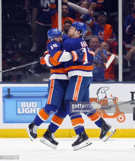 Cal Clutterbuck of the New York Islanders celebrates his third period goal against the Pittsburgh Penguins and is joined by Matt Martin in Game Three...