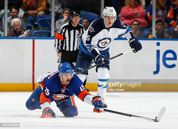 Cal Clutterbuck of the New York Islanders clears the puck away from Mark Scheifele of the Winnipeg Jets at Nassau Veterans Memorial Coliseum on...