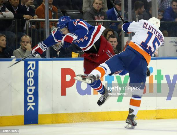 Cal Clutterbuck of the New York Islanders hits Justin Falk of the New York Rangers during the third period at Madison Square Garden on December 20...
