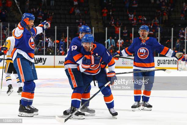 Cal Clutterbuck of the New York Islanders is congratulated by his teammates after his second goal against the Pittsburgh Penguins during the third...