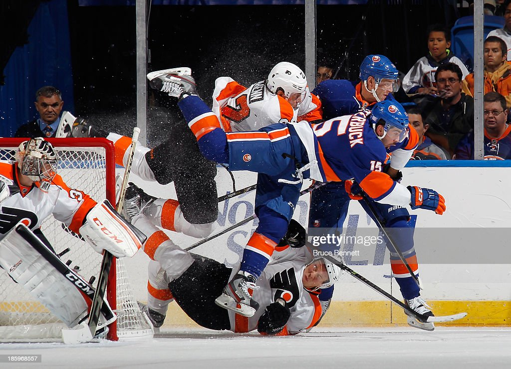Cal Clutterbuck #15 of the New York Islanders knocks over a couple of Philadelphia Flyers as he crashes the crease at the Nassau Veterans Memorial Coliseum on October 26, 2013 in Uniondale, New York.