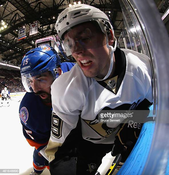 Cal Clutterbuck of the New York Islanders rides David Perron of the Pittsburgh Penguins into the glass during the second period at the Nassau...