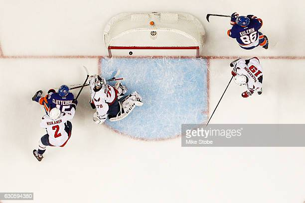 Cal Clutterbuck of the New York Islanders shoots the puck past Braden Holtby of the Washington Capitals for a first period goal at the Barclays...
