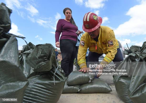 Cal Fire Captain Aldo Aleman shows Jennifer Hom how to properly use sandbags at the Sycamore Creek fire station in Corona in preparation for possible...