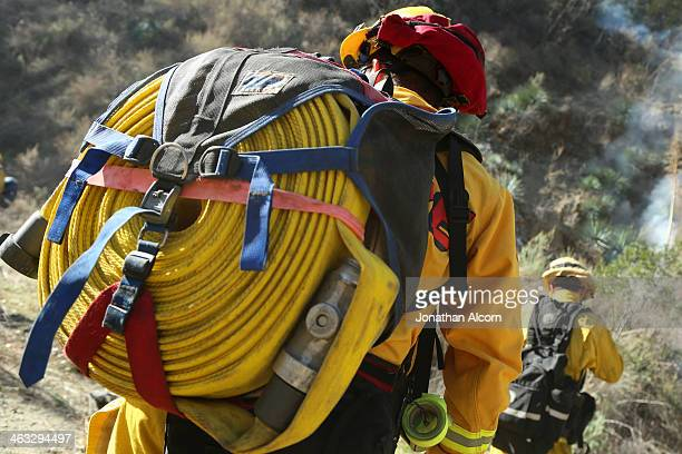 Cal Fire crew carries a fire line on his back at a flareup of the Colby Fire burning for a second day in the hillside above Highway 39 on January 17...