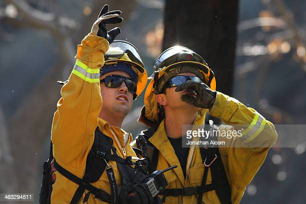 Cal Fire crew work at a flareup at the Colby Fire burning for a second day in the hillside above Highway 39 on January 17 2014 in Azusa California...