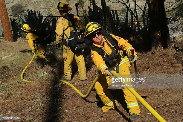 Cal Fire crew work on a flareup at the Colby Fire burning for a second day in the hillside above Highway 39 on January 17 2014 in Azusa California...