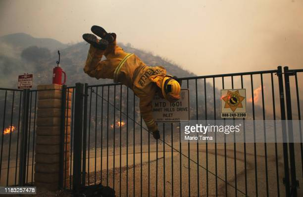 Cal Fire firefighter hops over a locked gate while working the Tick Fire on October 24 2019 in Canyon Country California The fire has burned at least...