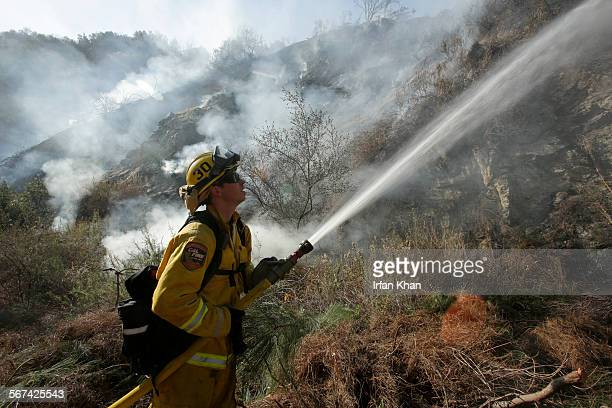 Cal Fire firefighter Jeff Newby Engine 3480 shoots water on smoldering brush on a hillside along Highway 39 in Azusa The Colby fire that has been...