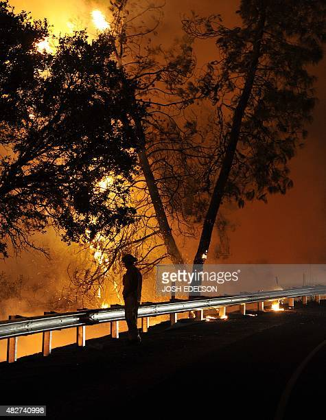 Cal Fire firefighter Julio Castillo looks towards flames of the Rocky fire as they approach Highway 20 near Clear Lake California on August 2 2015...