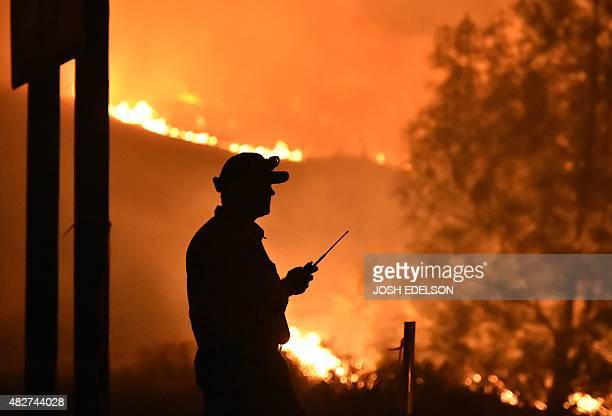 A Cal Fire firefighter keeps an eye on the Rocky fire near Clear Lake California on August 2 2015 The fire has charred more than 27000 acres and is...