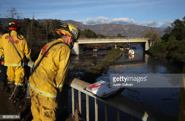 Cal Fire firefighter looks at a flooded section of Highway 101 after a mudslide on January 10 2018 in Montecito California 17 people have died and...