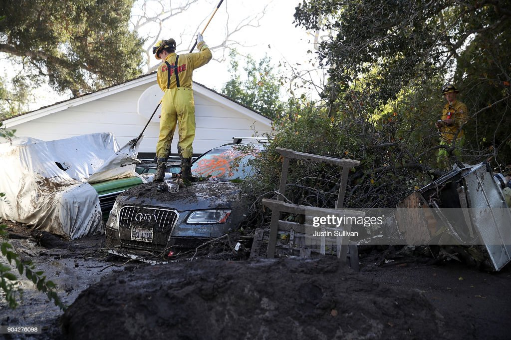 A Cal Fire firefighter looks through a car next to a home that was destroyed by a mudslide on January 12, 2018 in Montecito, California. 17 people have died and hundreds of homes have been destroyed or damaged after massive mudslides crashed through Montecito, California early Tuesday morning.