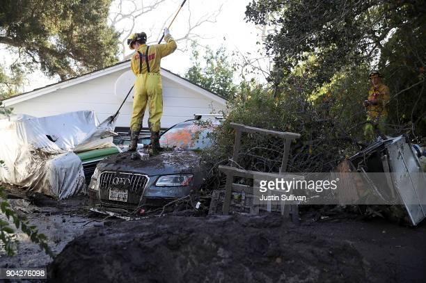 Cal Fire firefighter looks through a car next to a home that was destroyed by a mudslide on January 12 2018 in Montecito California 17 people have...