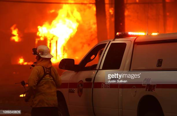 Cal Fire firefighter monitors a burning home as the Camp Fire moves through the area on November 8, 2018 in Paradise, California. Fueled by high...
