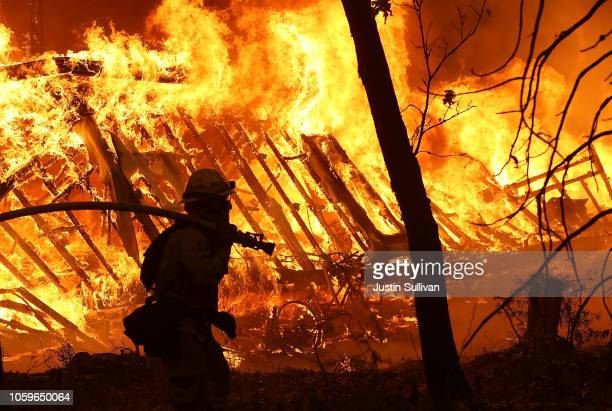 Cal Fire firefighter monitors a burning home as the Camp Fire moves through the area on November 9 2018 in Magalia California Fueled by high winds...