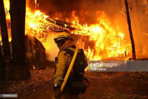 Cal Fire firefighter monitors a burning home as the Camp Fire moves through the area on November 9, 2018 in Magalia, California. Fueled by high winds...