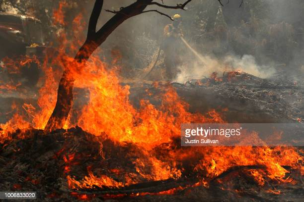 Cal Fire firefighter mops up hot spots after the Carr Fire moved through the area on July 28 2018 in Redding California A Redding firefighter and...