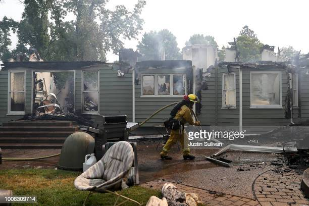 Cal Fire firefighter pulls a hose in front of a home that was destroyed by the Carr Fire on July 27 2018 in Redding California A Redding firefighter...