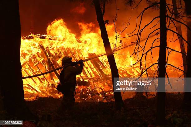 Cal Fire firefighter sprays water on a home next to a burning home as the Camp Fire moves through the area on November 9 2018 in Magalia California...