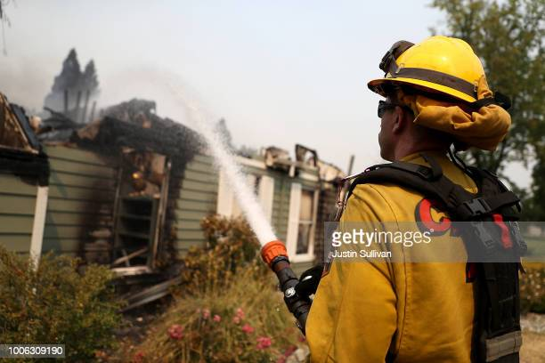 Cal Fire firefighter sprays water on a home that was destroyed by the Carr Fire on July 27 2018 in Redding California A Redding firefighter and...