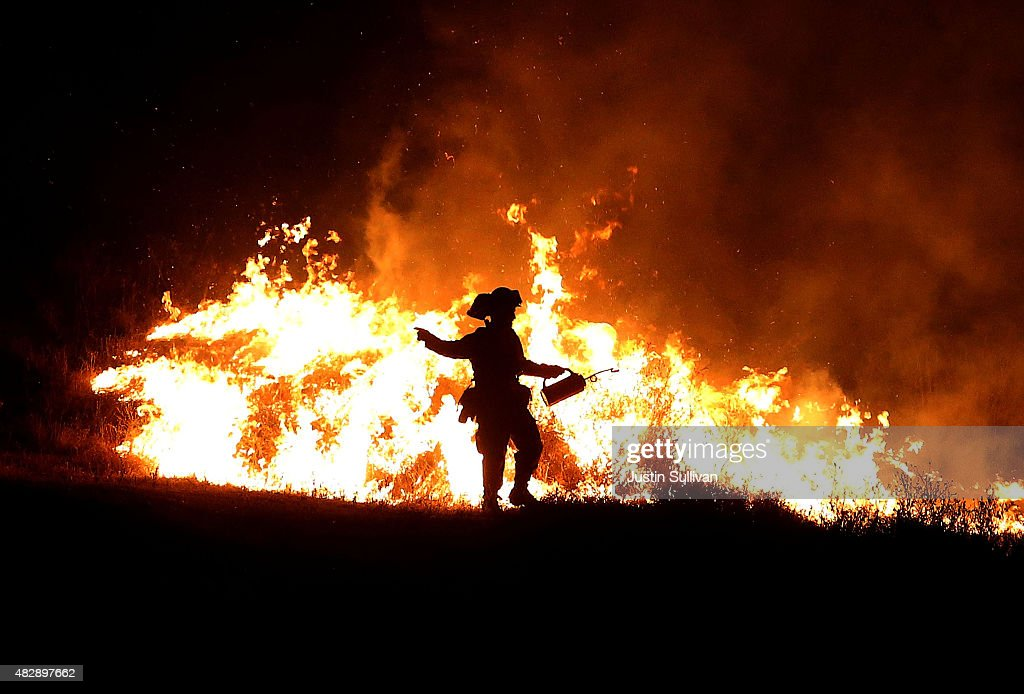 A Cal Fire firefighter uses a drip torch to start a backfire as he battles the Rocky Fire on August 3, 2015 near Clearlake, California. Nearly 3,000 firefighters are battling the Rocky Fire that has burned over 60,000 acres has forced the evacuation of 12,000 residents in Lake County. The fire is currently 12 percent contained and has destroyed at least 14 homes. 6,300 homes are threatened by the fast moving blaze.