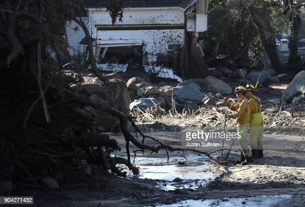 Cal Fire firefighters search a neighborhood that was destroyed by a mudslide on January 12 2018 in Montecito California 17 people have died and...