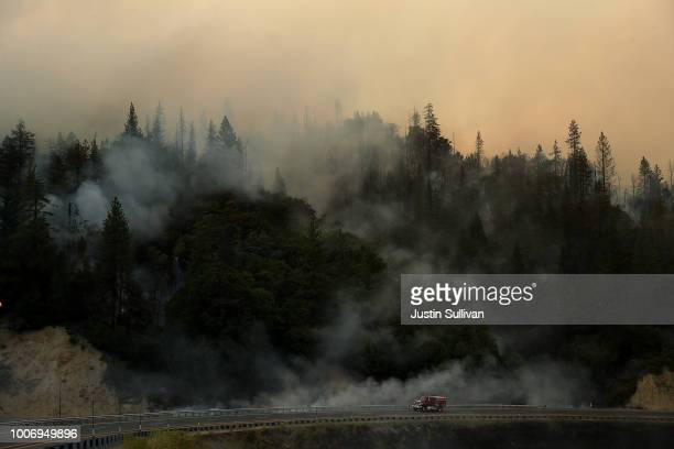 Cal Fire truck drives along highway 299 as the Carr Fire burns in the hills on July 28 2018 neat Whiskeytown California A Redding firefighter and a...