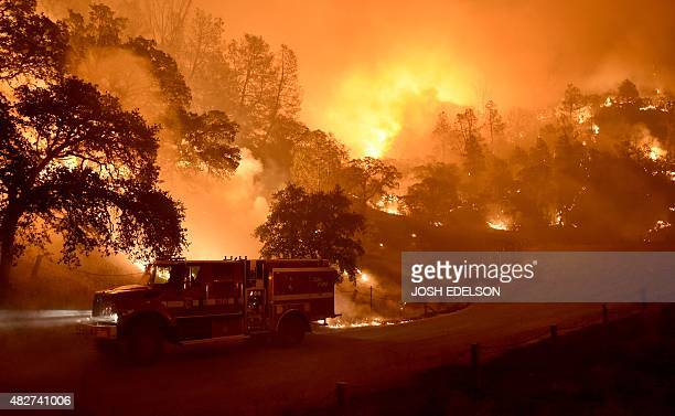 A Cal Fire truck is driven away from flames as the Rocky fire burns near Clear Lake California on August 2 2015 The fire has charred more than 27000...
