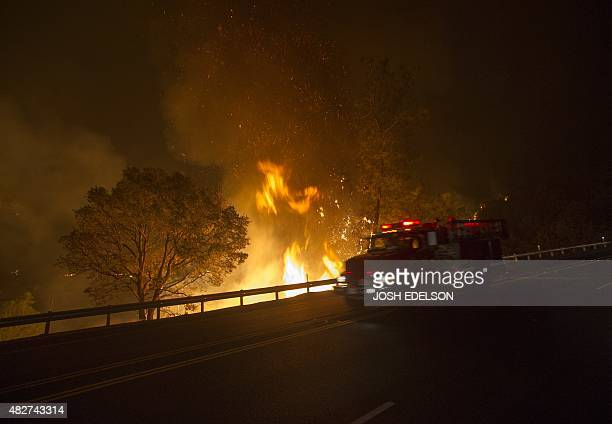 A Cal Fire truck passes an advancing flame as it approaches Highway 20 during the Rocky fire near Clear Lake California on August 2 2015 The fire has...