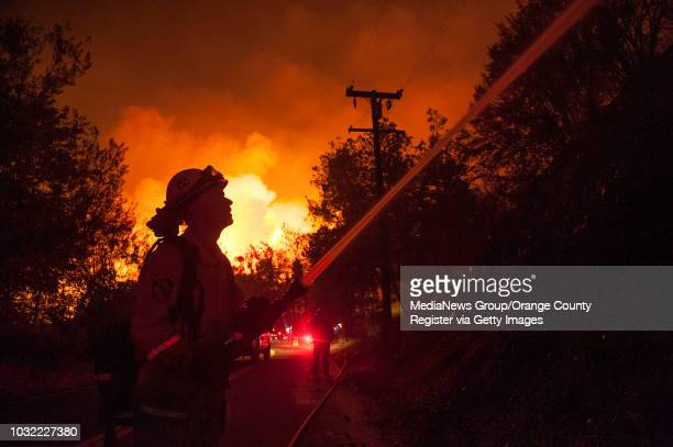 Cal Fire's Keith Vitale sprays a hot spot along Lytle Creek Rd while fighting the Blue Cut Fire Wednesday night