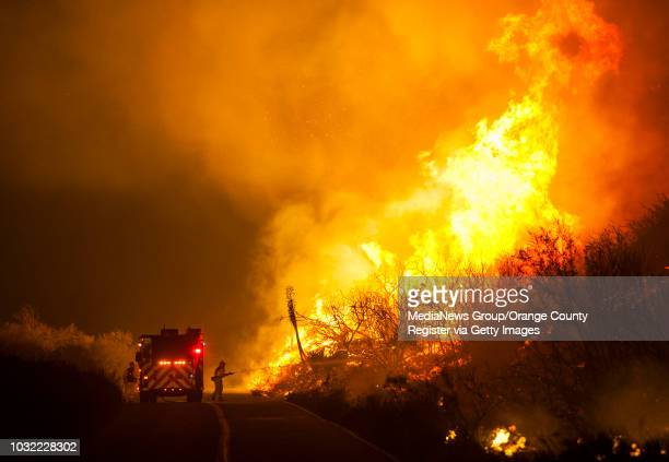 Cal Fire's Steve Rodberg of Laguna Niguel sprays water on flames while battling the Blue Cut Fire along Lytle Creek Rd Wednesday night