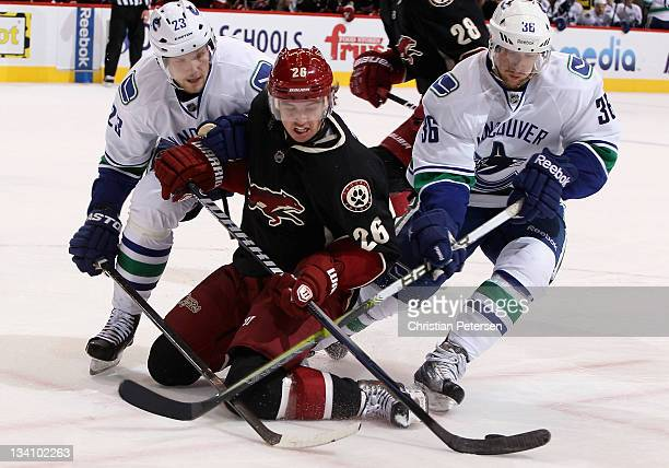 Cal O'Reilly of the Phoenix Coyotes attempts to control the puck under pressure from Alexander Edler and Jannik Hansen of the Vancouver Canucks...