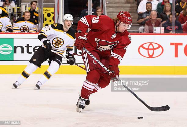 Cal O'Reilly of the Phoenix Coyotes skates witih the puck past Benoit Pouliot of the Boston Bruins during the NHL game at Jobingcom Arena on December...