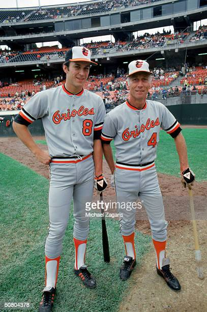 Cal Ripken Jr #8 and Cal Ripken Sr #4 of the Baltimore Orioles lean on their bats prior to a game against the Athletics at OaklandAlameda County...