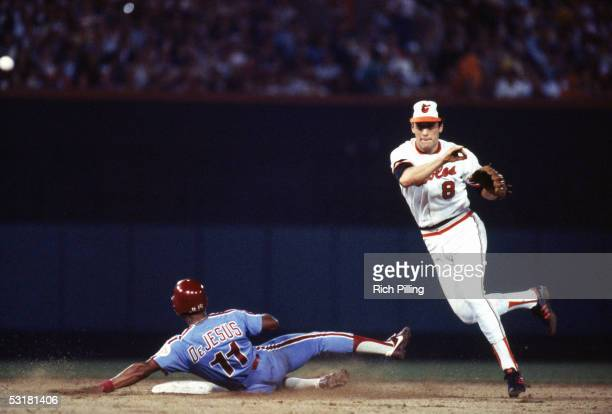 Cal Ripken Jr #8 of the Baltimore Orioles attempts to complete a double play as he throws over Ivan DeJesus of the Philadelphia Phillies during a...