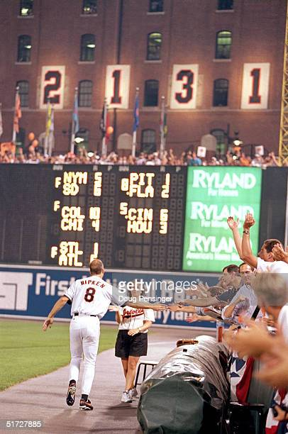 Cal Ripken Jr #8 of the Baltimore Orioles highfives fans along side the warning track as he celebrates breaking Lou Gehrig's record for consecutive...