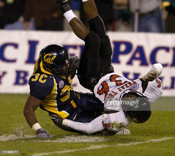 Cal running back JJ Arrington and Texas cornerback Antonio Huffman colide during the Pacific Life Holiday Bowl at Qualcomm Stadium in San Diego Calif...