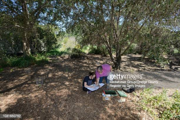 Cal State Fullerton student Katie Rummel left and grad student Donna Rader map the location of sprinkler valves at the Fullerton Arboretum on Friday...