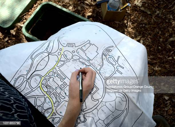 Cal State Fullerton student Katie Rummel makes locations of sprinkler valves on a map of the Fullerton Arboretum on Friday Rummel and grad student...