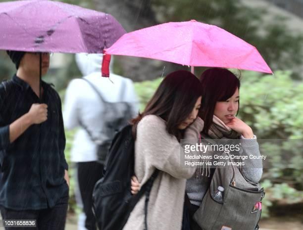 Cal State Fullerton students Rabi Sasaki, left, and Mizuho Yoshie, huddle under umbrellas as they dodge a downpour on Monday, Sasaki is an...