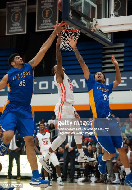Cal State Fullerton's Alex Harris scores past San Jose State's Matt Pollard left and Jalen James during the Titans' 7066 victory over the Spartans...