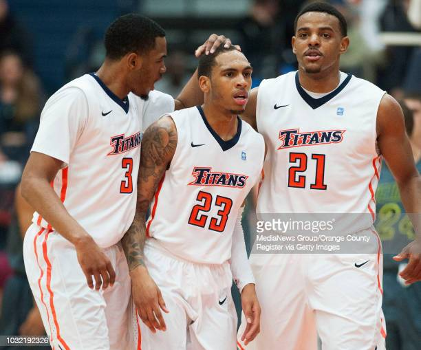 Cal State Fullerton's Moses Morgan left and Steve McClellan right comfort Alex Harris after a foul call during the Titans' 6358 loss to UC Irvine at...