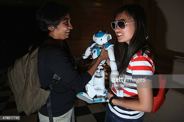Cal Tech post-doctorial student Vasu Raman passes a $15,000 NAO robot to Cornell University Mechanical Engineering PhD candidate Catherine Wong while...