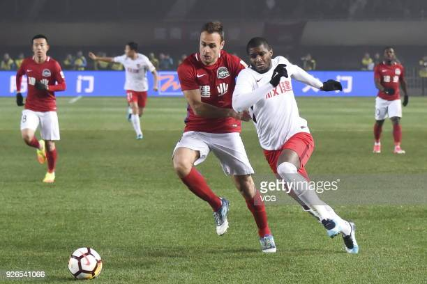Cala of Henan Jianye and Anthony Modeste of Tianjin Quanjian compete for the ball during the 2018 Chinese Football Association Super League first...