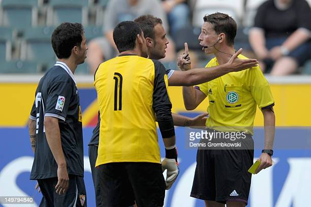 Cala of Sevilla argues with referee Christian Bandurski during the friendly match between Borussia Moenchengladbach and FC Sevilla at BorussiaPark on...
