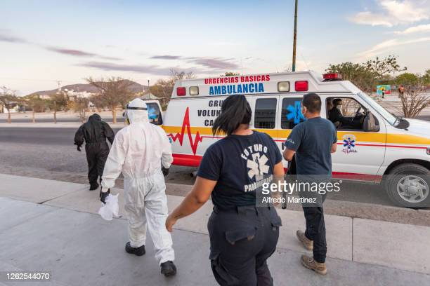 Calafia paramedics wearing PPE are seen walking to an ambulance on July 28, 2020 in La Paz, Mexico. Many Mexican States remain in orange emergency...