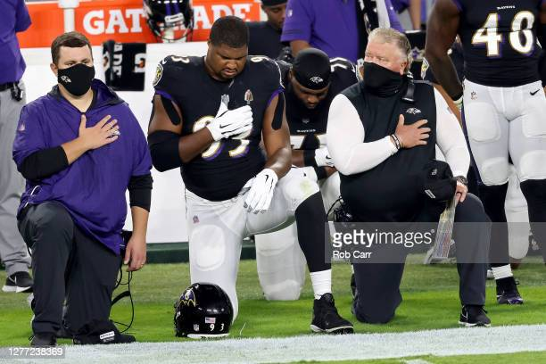 Calais Campbell of the Baltimore Ravens and defensive coordinator Don Martindale kneel during the national anthem prior to the game at M&T Bank...